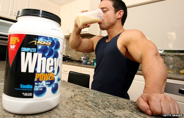 A large tub of whey protein powder sits on a kitchen worktop as a bodybuilder takes a drink