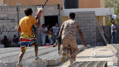 Members of security forces run away from clashes in Benghazi on 8 June