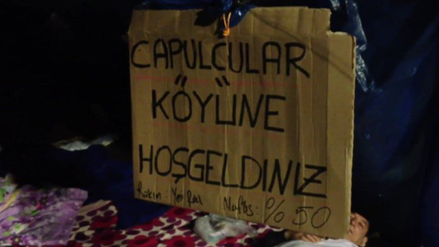 Sign by protesters saying 'welcome to Riffraff village'