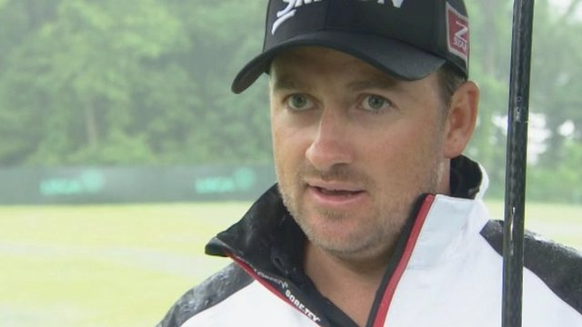 Graeme McDowell takes cover under an umbrella after Monday's practice was abandoned at Merion