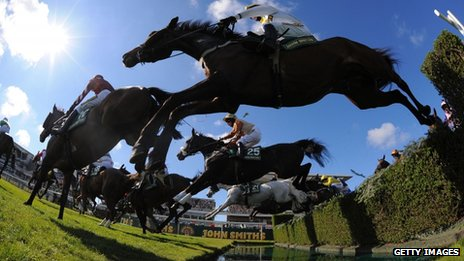 A horse ridden by Samantha Drake jumps the water during the first day of the 2013 Grand National meet