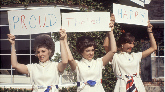 Astronauts' wives hold up signs