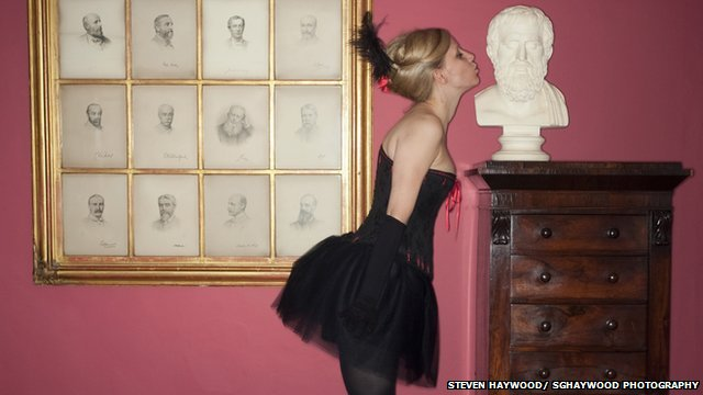 Burlesque performer kissing sculpted head on antique drawers