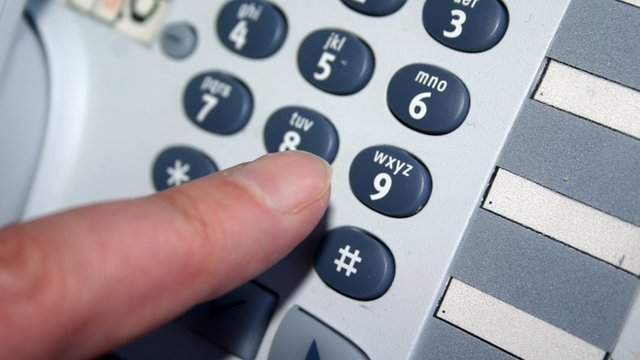 A person dialling 9 on a telephone