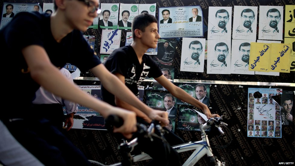 Iranian youths ride their bicycles past campaign posters of Mohsen Rezai, conservative presidential candidate and former chief of the Revolutionary Guards, and candidates for the municipality election in central Tehran