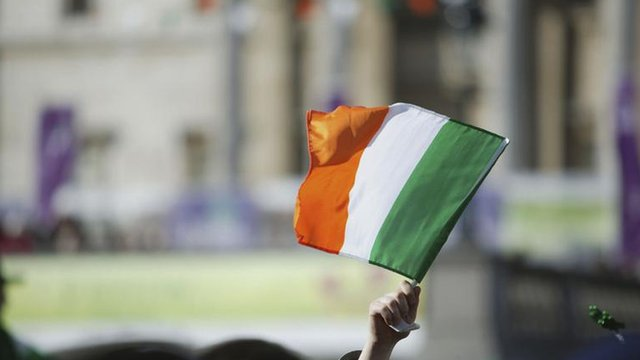 An Irish flag is held aloft