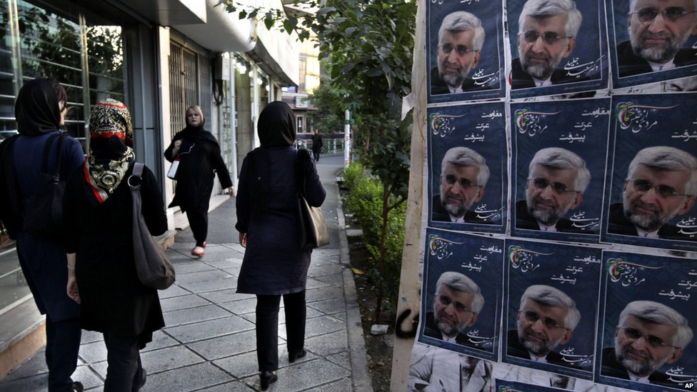 Iranian women walk past photos of conservative presidential candidate, Saeed Jalili, the country's top nuclear negotiator