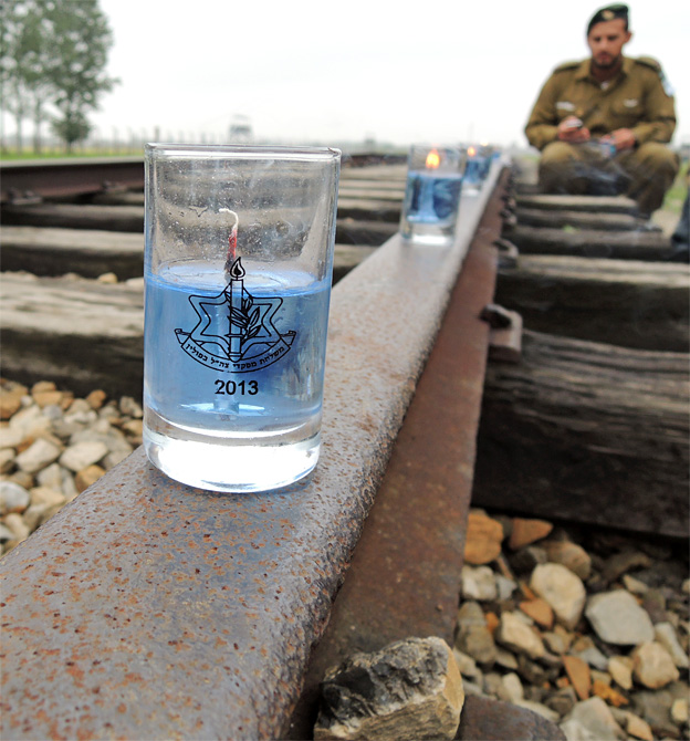 An Israeli soldier sits looking at the candles on the railway line