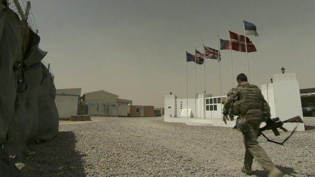 Soldier walks past memorial wall in Kabul barracks