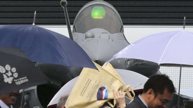 Visitors walk in front of a Dassault Rafale fighter on the first day of the rain-soaked 50th Paris Air Show, at Le Bourget airport near Paris