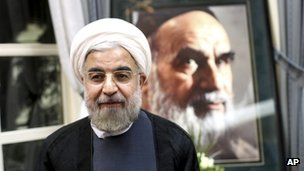 President elect Hassan Rouhani, stands in front of a portrait of the late Iranian Ayatollah Khomeini, during a visit to his shrine