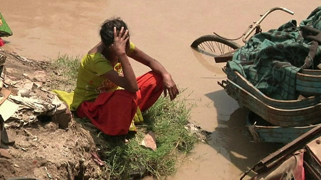 Woman with head in hands, surrounded by flood water