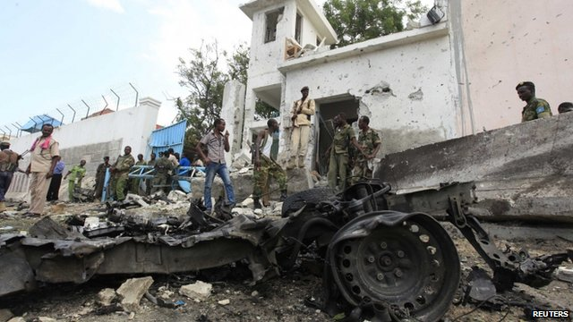 "Security agents stand near the scene of a suicide bomb attack outside the United Nations compound in Somalia""s capital Mogadishu"