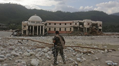 A member of the rescue operation team of Sashastra Seema Bal (SSB) or Armed Border Force walks towards the officers training centre damaged by floods at their campus in Srinagar in the Himalayan state of Uttarakhand