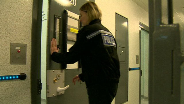 A police woman closing a cell door