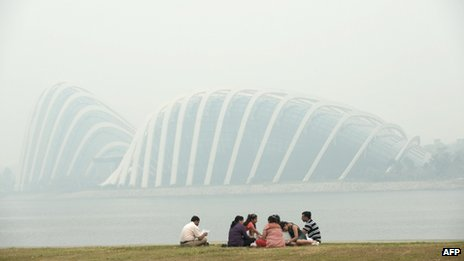 A group of people sit opposite the Garden by the Bay in Singapore on 20 June 2013