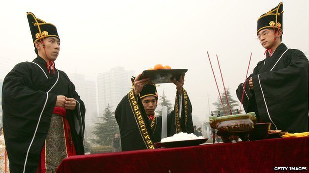 People dressed in traditional costumes of Han nationality, offer fruits as scarifices to Heaven