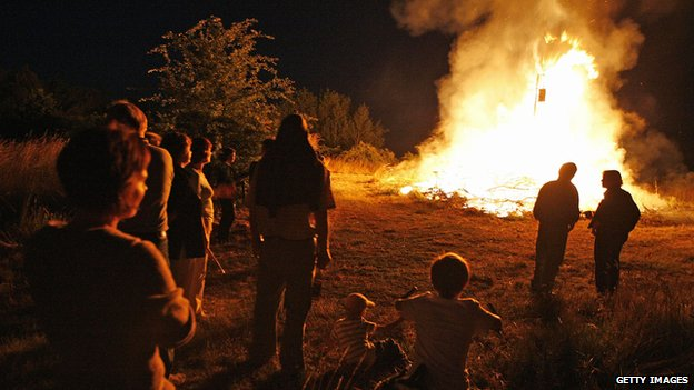 People watch a traditional midsummer festival bonfire to mark the summer solstice