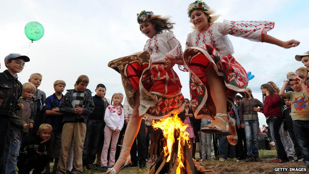 Girls jump over a fire during celebrations for Ivan Kupala, the feast of St John the Baptist, a traditional Slavic orthodox holiday celebrating the summer solstice