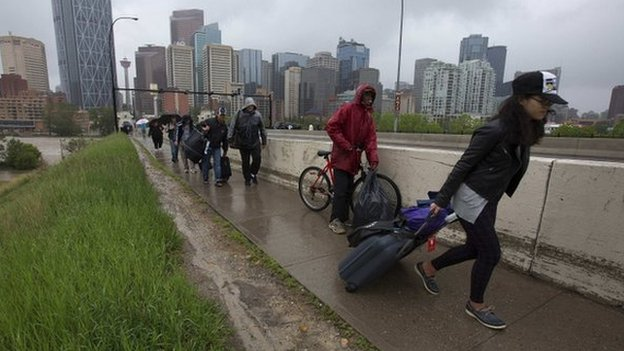 Residents leave the flooding downtown core as new orders evacuating all of downtown were issued in Calgary, Alberta 21 June 2013