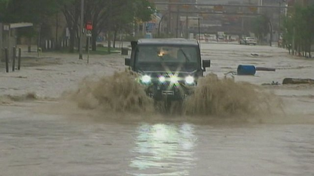Four-wheel drive vehicle driving through flooded street