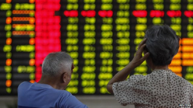 Elderly couple in front of stock market boards