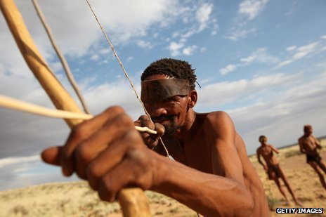 A hunter gatherer aims his bow and arrow