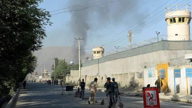 Afghan security forces stand guard as smoke rises from the entrance gate of the presidential palace in Kabul