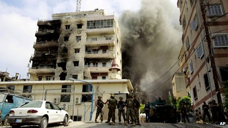 Lebanese soldiers stand by as black smoke rises from a mosque in Sidon where Sunni cleric Sheik Ahmad al-Assir preaches