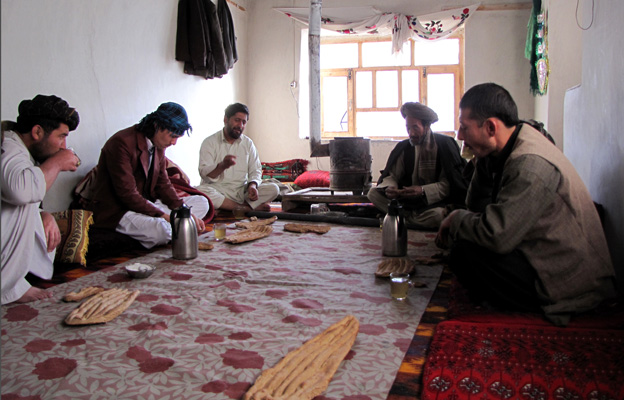 Men sitting cross-legged, sharing a breakfast