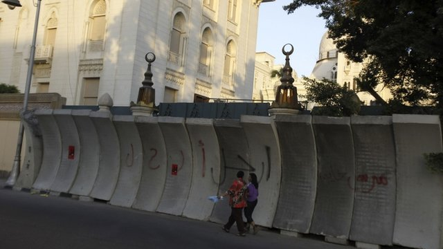 People walk in front of new concrete barricades erected to prevent any attacks at El-Thadiya presidential palace in Cairo