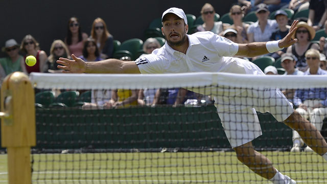 Viktor Troicki attempts to hit the ball with his hand after dropping his racket