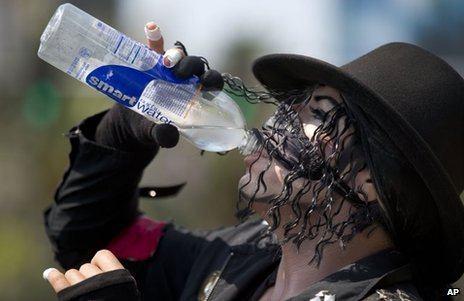 Michael Jackson impersonator Juan Carlos Gomez drinks some water as he takes a break from posing for photos with tourists along The Strip in Las Vegas on Friday