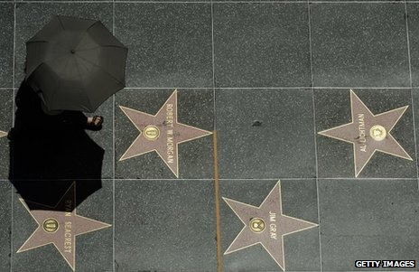 A tourist holding an umbrella to shield herself from the sun walks on Hollywood Walk of Fame stars during a major heat wave in Southern California on Friday