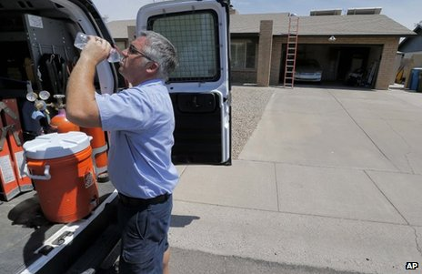 Air conditioning technician Michael Hawks cools off after inspecting a unit in Phoenix, Arizona, on Friday