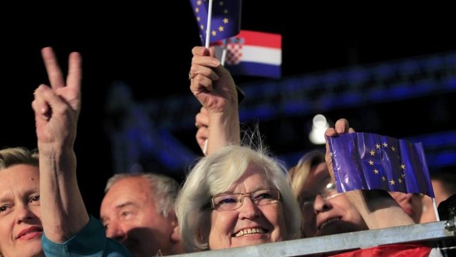 A woman makes victory sign as she holds the EU flag during the celebration of the accession of Croatia to the EU in Zagreb