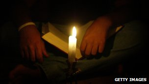 Man reads the Bible by candlelight in Syria monastery