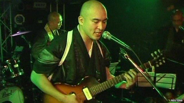 Reverend Kazuhiro Sekino plays guitar