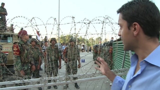 The BBC's Aleem Maqbool stands in front of barbed wire at a pro-Morsi march