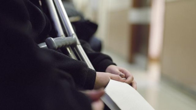 Unidentified patient with crutches holds paperwork