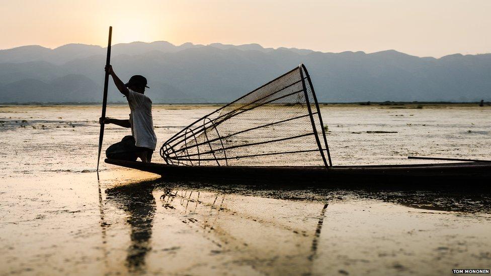A fisherman on Inle Lake at sunset in Burma