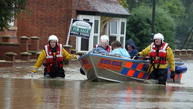 A fire rescue boat takes people from their home after heavy flooding