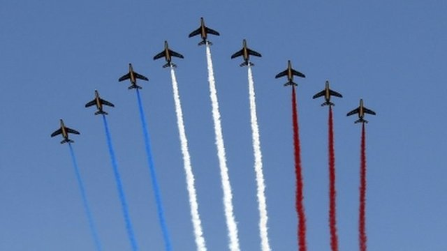 Nine jets from the French Air Force Patrouille de France releasing trails of red, white and blue smoke