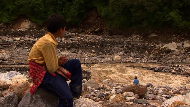 Boy and woman sitting near river