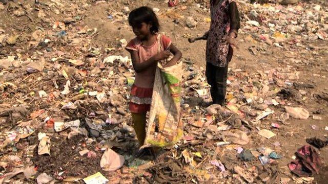 Indian girl picking up rubbish