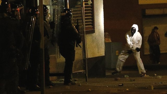 A loyalist rioter attacks riot police in the Woodvale area of north Belfast, Northern Ireland, Monday, July 15, 2013