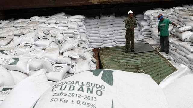 """Workers stand on top of bags labelled """"Cuban raw sugar"""" inside a North Korean flagged ship"""