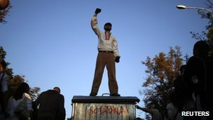 A protester gestures atop a garbage bin with the word 'Resign!' on it