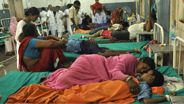 A mother rests with her sick son in a hospital in Patna on 17 July 2013