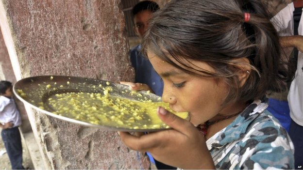 An Indian girl eats her free school lunch at a government run school in Patna on 17 July 2013